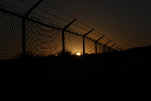 The sun sets behind a border fence separating Del Rio, Texas, and Ciudad Acuna, Mexico, Thursday, Sept. 23, 2021. Each year, the border communities that sit across the Rio Grande from one another come together to celebrate the Fiesta de la Amistad.