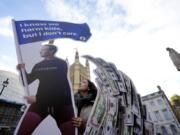Senior campaigner from SumOfUs Flora Rebello Arduini adjusts an installation outside parliament in Westminster in London, Monday, Oct. 25, 2021. A 4-metre-high installation depicting Mark Zuckerberg surfing on a wave of cash was constructed outside parliament, as Facebook whistleblower Frances Haugen is due to testify to MPs on how the company puts profits ahead of public safety. The action comes after SumOfUs research revealed Instagram is still awash with posts promoting eating disorders, unproven diet supplements and skin-whitening products.