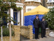 FILE - In this Sunday, Oct. 17, 2021 file photo, police officers stand outside a house in north London, thought to be in relation to the death of member of Parliament David Amess. The killing of British lawmaker Amess is once again fueling concern about a government program that tries to prevent at-risk young people from becoming radicalized, with critics saying the strategy is falling short and unfairly targets Muslim communities.