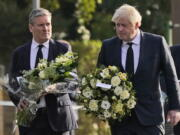 British Prime Minister Boris Johnson, right, and Leader of the Labour Party Keir Starmer carry flowers as they arrive at the scene where a member of Parliament was stabbed Friday, in Leigh-on-Sea, Essex, England, Saturday, Oct. 16, 2021. David Amess, a long-serving member of Parliament was stabbed to death during a meeting with constituents at a church in Leigh-on-Sea on Friday, in what police said was a terrorist incident. A 25-year-old man was arrested in connection with the attack, which united Britain's fractious politicians in shock and sorrow.