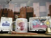"""Windsor Castle is reflected in the window of a shop selling Royal souvenirs outside the Castle, in Windsor, England, Friday, Oct. 22, 2021. Britain's Queen Elizabeth II spent a night in a hospital for checks this week after canceling an official trip to Northern Ireland on medical advice, Buckingham Palace said Thursday. The palace said the 95-year-old British monarch went to the private King Edward VII's Hospital in London on Wednesday for """"preliminary investigations."""" It said she returned to her Windsor Castle home at lunchtime on Thursday, """"and remains in good spirits."""