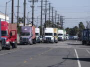 Parked cargo container trucks are seen in a street, Wednesday, Oct. 20, 2021 in Wilmington, Calif. California Gov. Gavin Newsom on Wednesday issued an order that aims to ease bottlenecks at the ports of Los Angeles and Long Beach that have spilled over into neighborhoods where cargo trucks are clogging residential streets. (AP Photo/Ringo H.W. Chiu) (Ringo H.W.