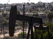 FILE - In this May 18, 2021, file photo, homes sit on a hill behind pump jacks operating at the Inglewood Oil Field in Los Angeles. California's oil regulator wants to ban new oil and gas drilling within 3,200 feet of schools, homes and hospitals to protect public health. The draft rule released Thursday, Oct. 21, 2021, would be the nation's largest buffer zone between drilling and community sites if adopted. (AP Photo/Jae C.