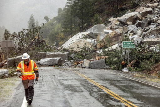 Caltrans maintenance supervisor Matt Martin walks by a landslide covering Highway 70 in the Dixie Fire zone on Sunday, Oct. 24, 2021, in Plumas County, Calif. Heavy rains blanketing Northern California created slide and flood hazards in land scorched during last summer's wildfires.