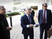 FILE - Fr. Paul Kalchik, left, St. Michael's Media founder and CEO Michael Voris, center, and Milo Yiannopoulos talk with a court officer before entering the federal courthouse, Sept. 30, 2021 in Baltimore. A federal judge has blocked Baltimore city officials from banning the conservative Roman Catholic media outlet from holding a prayer rally at a city-owned pavilion during a U.S. bishops' meeting next month. U.S. District Judge Ellen Hollander ruled late Tuesday, Oct. 13, 2021 that St. Michael's Media is likely to succeed on its claims that the city discriminated against it on the basis of its political views and violated its First Amendment free speech rights.
