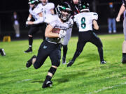Dalton Beassie carries the ball in Woodland's 8-7 win over R.A. Long at Longview Memorial Stadium on Oct. 8. Beassie finished with 104 yards and a touchdown on 21 carries.