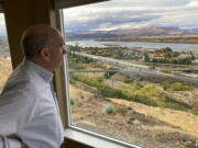 In this Tuesday, Oct. 5, 2021, photo, The Dalles Mayor Richard Mays looks at the view of his town and the Columbia River from his hilltop home in The Dalles, Oregon. Mays helped negotiate a proposal by Google to build new data centers in the town. The data centers require a lot of water to cool their servers, and would use groundwater and surface water, but not any water from the Columbia River.