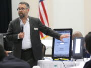 FILE - In this Aug. 30, 2018 file photo, Eric Coomer from Dominion Voting demonstrates his company's touch screen tablet that includes a paper audit trail at the second meeting of Secretary of State Brian Kemp's Secure, Accessible & Fair Elections Commission in Grovetown, Ga. Attorneys for President Donald Trump's re-election campaign, its onetime attorney Rudy Giuliani and conservative media figures asked a judge Wednesday, Oct. 13, 2021, to dismiss a defamation lawsuit by Coomer, a former employee of Dominion Voting Systems, who argues he lost his job after being named in false charges as trying to rig the 2020 election.