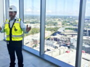 Kevin Lavallee, CEO of TK Elevators' North American operations, stands at the top of the company's new elevator testing facility, Wednesday, Oct. 13, 2021, that towers over the Atlanta Braves stadium and surrounding skyscrapers northwest of Atlanta. The 420-foot-tall tower is set to become fully operational early next year.