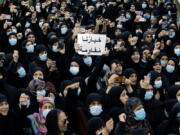 """FILE - In this Oct. 15, 2021, mourners chant slogans as they hold a placard with Arabic that reads """"Our choice is resistance"""" during the funeral of three Hezbollah supporters who were killed during clashes, in the southern Beirut suburb of Dahiyeh, Lebanon. Internal company documents from the former Facebook product manager-turned-whistleblower Frances Haugen show that in some of the world's most volatile regions, terrorist content and hate speech proliferate because the company remains short on moderators who speak local languages and understand cultural contexts."""