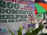 A woman stands beside a sign about hiring domestic helpers for the Mideast outside an office in Manila, Philippines on Thursday, Oct. 21, 2021. The Philippines, a leading source of global labor, has fought with alarm the spike in the number of Facebook pages, which have been used for illegal job recruitment and human trafficking in the last two years. Facebook suggested a pilot program to begin in 2021 that targeted Filipinas with pop-up messages and banner ads warning them about the dangers working overseas can pose.