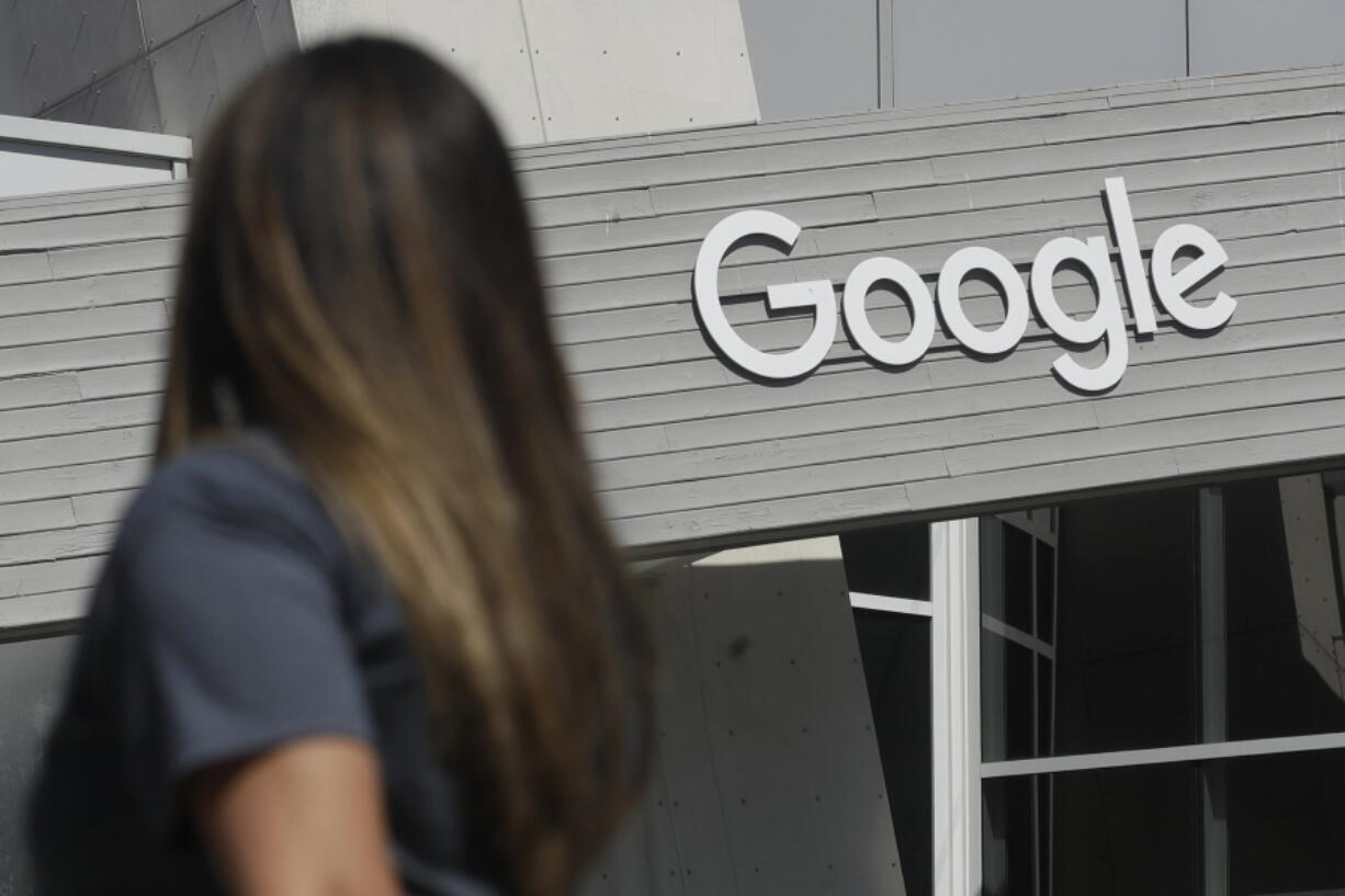 FILE - In this Sept. 24, 2019, file photo, a woman walks below a Google sign on the campus in Mountain View, Calif.  Google on Thursday, Oct. 7, 2021, will no longer allow digital ads promoting false climate change claims to appear next to the content of other publishers, hoping to deny money to those making such claims and to stop the spread of misinformation on its platform.