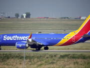 FILE - In this July 2, 2021, file photo, a Southwest Airlines jetliner taxis down a runway for take off from Denver International Airport in Denver. Southwest Airlines canceled hundreds more flights Monday, Oct. 11, 2021 following a weekend of major service disruptions. By midmorning Monday, Southwest had canceled about 360 flights and more than 600 others were delayed.