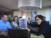 Anna Salton Eisen holds up a photo of Emil Ringel, father of Barbara Ringel, for a Zoom video call during a gathering for families of Holocaust survivors in East Brunswick, N.J., on Sunday, Sept. 26, 2021. Seventy-six years after American soldiers cut down the barbed wire and fulfilled the prisoners' impossible dream of freedom, Eisen brought together survivors' loved ones.