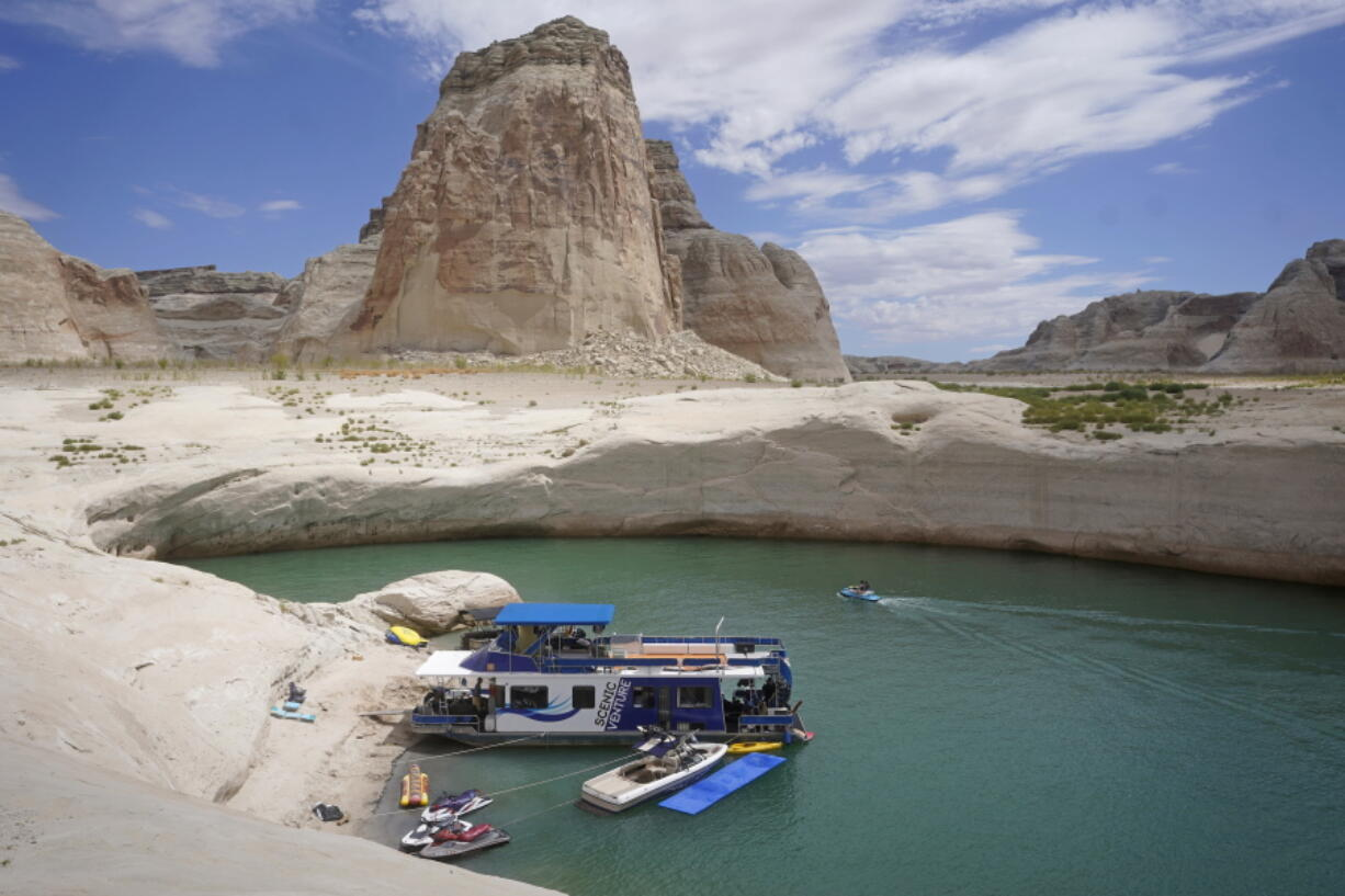 FILE - In this Friday, July 30, 2021 file photo, a houseboat rests in a cove at Lake Powell near Page, Ariz. This summer, the water levels hit a historic low amid a climate change-fueled megadrought engulfing the U.S. West.  Severe drought across the West drained reservoirs this year, slashing hydropower production and further stressing the region's power grids. And as extreme weather becomes more common with climate change, grid operators are adapting to swings in hydropower generation.