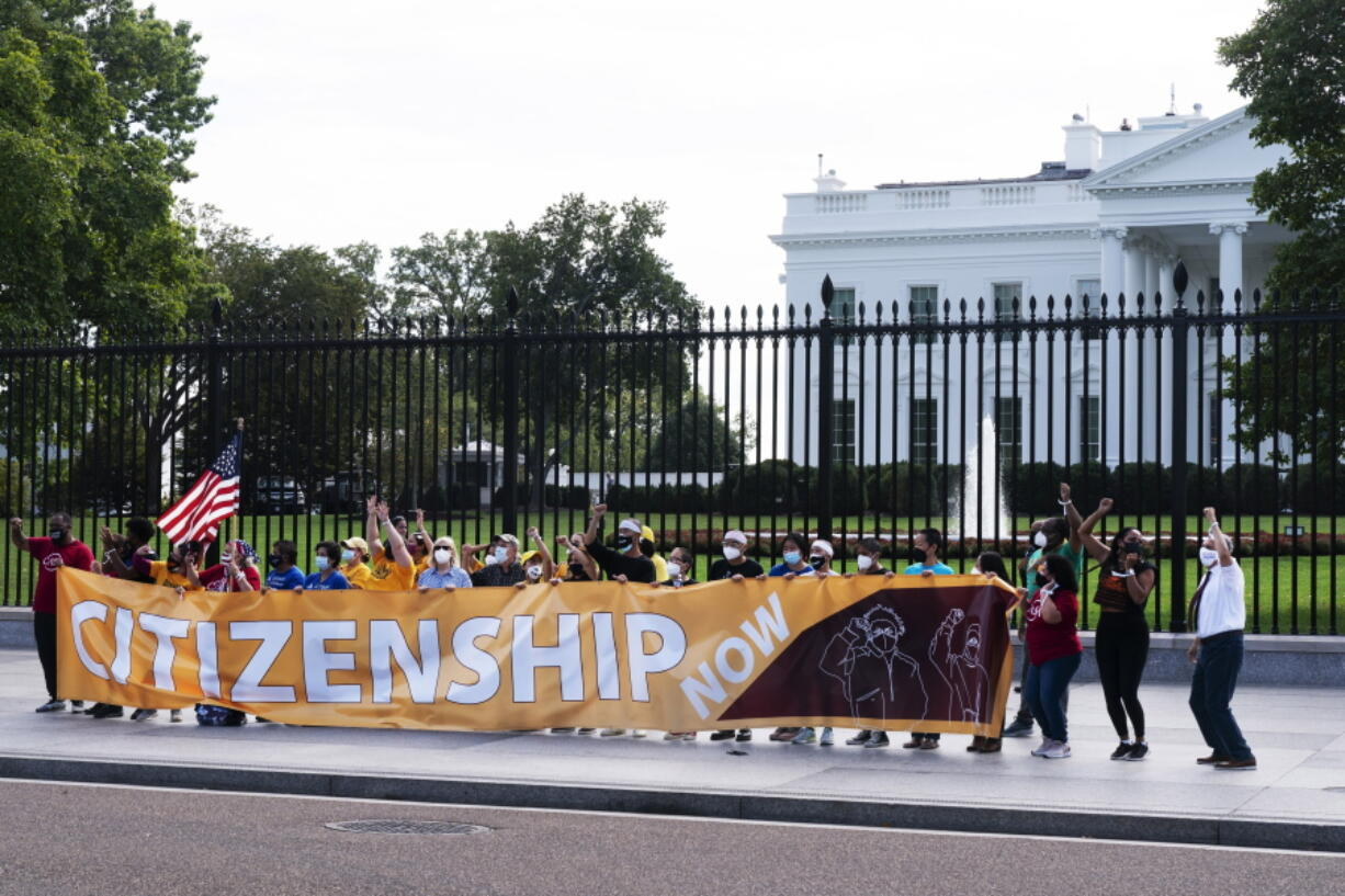 Protesters risk arrest as they rally on the sidewalk by the White House on Pennsylvania Avenue, Thursday, Oct. 7, 2021, in Washington. The protesters urged Vice President Kamala Harris and Senate Democrats to include immigration reform in the reconciliation package.