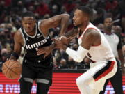 Sacramento Kings guard De'Aaron Fox, left, tries to get past Portland Trail Blazers guard Damian Lillard during the first half of an NBA basketball game in Portland, Ore., Wednesday, Oct. 20, 2021.