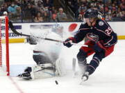 Seattle Kraken goalie Philipp Grubauer, left, stops a shot by Columbus Blue Jackets forward Patrik Laine during the second period of an NHL hockey game in Columbus, Ohio, Saturday, Oct. 16, 2021.