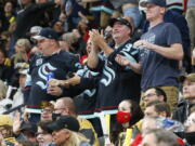 Seattle Kraken fans celebrate the team's goal against the Vegas Golden Knights during the second period of an NHL hockey game Tuesday, Oct. 12, 2021, in Las Vegas.