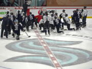 Seattle Kraken players kneel on the ice at their training facility as head coach Dave Hakstol outlines a play during NHL hockey practice, Thursday, Oct. 21, 2021, in Seattle. The Kraken will face the Vancouver Canucks, Saturday in Seattle for the expansion team's home opener. (AP Photo/Ted S.
