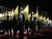 FILE - In this May 31, 2019 file photo, Hezbollah fighters march at a rally to mark Jerusalem day or Al-Quds day, in the southern Beirut suburb of Dahiyeh, Lebanon. On Monday, Oct. 18, 2021, Hezbollah leader Sheik Hassan Nasrallah revealed that his militant group has 100,000 trained fighters.