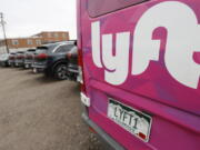 FILE - In this April 30, 2020, file photo, Kia Neros that are part of the Lyft ride-hailing fleet sit unused in a lot near Empower Field at Mile High in Denver.    Lyft says more than 1,800 sexual assaults were reported by riders in 2019, and the number of incidents has been rising sharply in recent years. Lyft posted the numbers in a new safety report, Friday, Oct. 22, 2021.