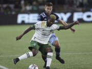 Portland Timbers forward Dairon Asprilla, right, controls the ball against Vancouver Whitecaps defender Marcus Godinho, left, during the first half of an MLS soccer match in Portland, Ore., Wednesday, Oct. 20, 2021.