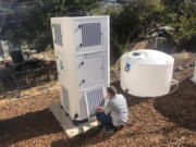 Ted Bowman, design engineer with Tsunami Products, installs an air-to-water unit in homeowner Don Johnson's backyard in Benicia, Calif.