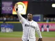FILE  - Former Seattle Mariners outfielder Ken Griffey Jr. waves to fans after being introduced before a baseball game against the Texas Rangers in Seattle, in this Friday, April 14, 2017, file photo. Hall of Famer Ken Griffey Jr. is investing in the Seattle Mariners in a way he never has before. He'll be part of the ownership going forward. The Mariners announced Monday, Oct. 25, 2021, that their most famous former player has also become the first one to purchase a stake in the ball club.