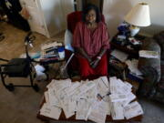 Debra Smith, 57, sits with her medical bills in her living room on Thursday, Oct. 7, 2021, in Spring Hill, Tenn. Smith, who has health problems that prevent her from working, has about $10,000 in unpaid medical bills. Patient advocates and some state governments say hospitals must do more to help patients deal with medical bills before the debt winds up in collections.