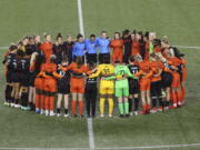 Portland Thorns and Houston Dash players, along with referees, gather at midfield Wednesday, in demonstration of solidarity with two former NWSL players who came forward with allegations of sexual harassment and misconduct against a former coach.