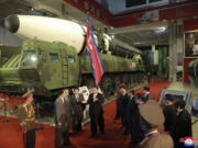 """In this photo provided by the North Korean government, North Korean leader Kim Jong Un, center, speaks in front of what the North says an intercontinental ballistic missile displayed at an exhibition of weapons systems in Pyongyang, North Korea, Monday, Oct. 11, 2021. Kim reviewed the rare exhibition and vowed to build an """"invincible"""" military, as he accused the United States of creating regional tensions and lacking action to prove it has no hostile intent toward the North, state media reported Tuesday. Independent journalists were not given access to cover the event depicted in this image distributed by the North Korean government. The content of this image is as provided and cannot be independently verified. Korean language watermark on image as provided by source reads: """"KCNA"""" which is the abbreviation for Korean Central News Agency."""