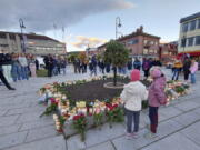 People gather around flowers and candles after a man killed several people on Wednesday afternoon, in Kongsberg, Norway, Thursday, Oct. 14, 2021.