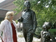 """FILE - In this Sept. 6, 2007 file photo, actor Betty Lynn, who played Thelma Lou on """"The Andy Griffith Show,"""" pauses at a statue of Andy and Opie Taylor in Mount Airy, N.C. Lynn died Saturday, Oct. 16, 2021, after a brief illness, The Andy Griffith Museum in Mount Airy announced in a statement.  She was 95."""