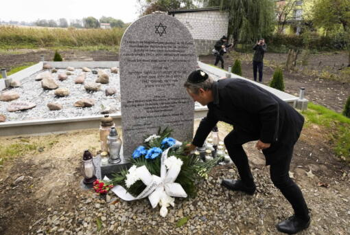 A man lays a candle at a new memorial at a mass grave to some 60 Jews, executed during the Holocaust in Wojslawice, Poland, on Thursday Oct. 14, 2021. It is one of many mass grave sites to be discovered in recent years in Poland, which during World War II was occupied by Adolf Hitler's forces.