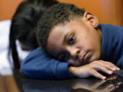 In this Sept. 23, 2021, photo Jhaimarion, 10, reacts as he listens to his mother, Krystal Archie talking with an Associated Press reporter in Chicago. Archie's three children were present when police, on two occasions, just 11 weeks apart, kicked open her front door and tore through their home searching for drug suspects. She'd never heard of the people they were hunting. Her oldest child, Savannah was 14 at the time; her youngest, Jhaimarion, was seven. They were ordered to get down on the floor.  (AP Photo/Nam Y.