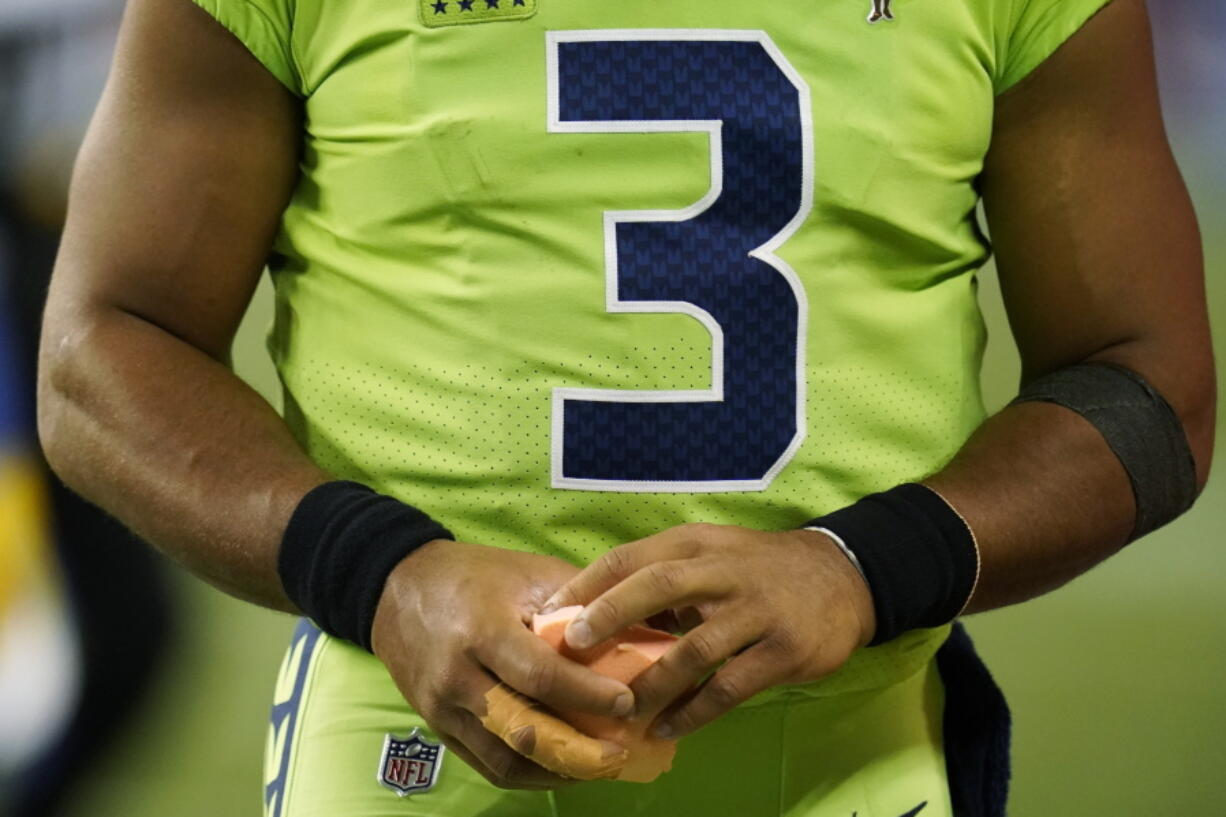Seattle Seahawks quarterback Russell Wilson holds a sponge near his taped injured finger during the fourth quarter of an NFL football game against the Los Angeles Rams, Thursday, Oct. 7, 2021, in Seattle. Wilson left the game after the injury and the Rams won 26-17.