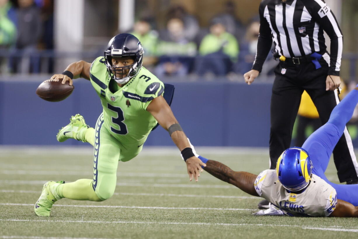 Seattle Seahawks quarterback Russell Wilson goes down as he tries to get a pass off against the Los Angeles Rams during the second half of an NFL football game, Thursday, Oct. 7, 2021, in Seattle.