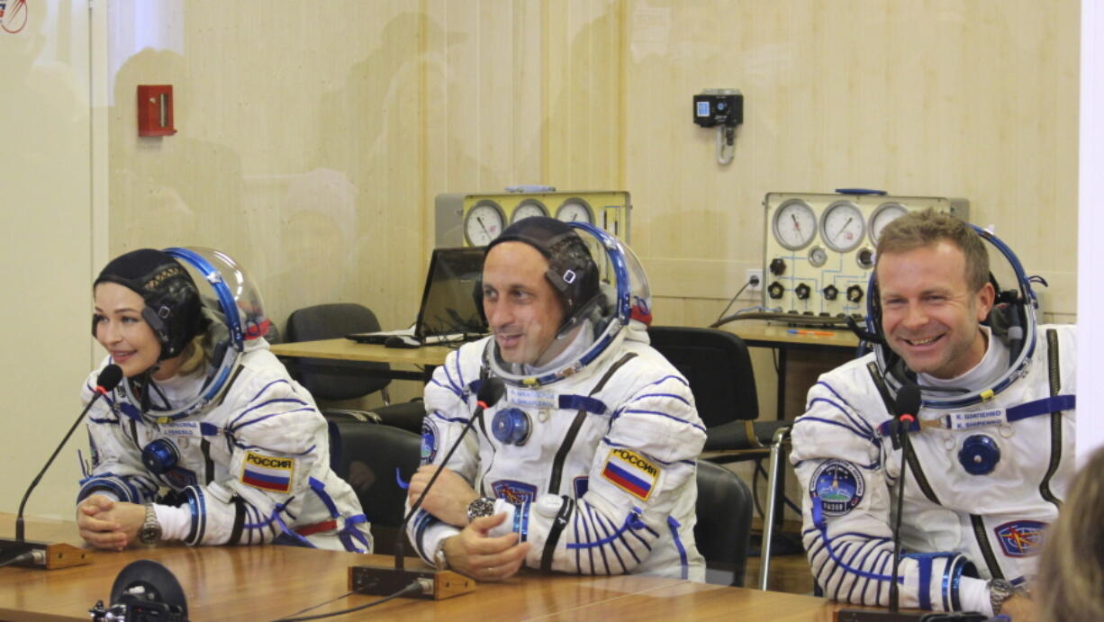 In this handout photo released by Roscosmos, actress Yulia Peresild, left, film director Klim Shipenko, right, and cosmonaut Anton Shkaplerov speak with their relatives through a safety glass prior the launch at the Baikonur Cosmodrome, Kazakhstan, Tuesday, Oct. 5, 2021. Actress Yulia Peresild and film director Klim Shipenko blasted off Tuesday for the International Space Station in a Russian Soyuz spacecraft together with cosmonaut Anton Shkaplerov, a veteran of three space missions, to make a feature film in orbit.