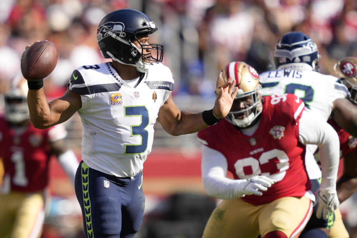 Seattle Seahawks quarterback Russell Wilson (3) passes in front of San Francisco 49ers defensive tackle D.J. Jones during the second half of an NFL football game in Santa Clara, Calif., Sunday, Oct. 3, 2021.