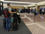 Passengers queue up at the ticketing counter for Southwest Airlines flights in Eppley Airfield Sunday, Oct. 10, 2021, in Omaha, Neb. Southwest Airlines canceled hundreds of flights over the weekend, blaming the woes on air traffic control issues and weather.