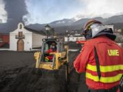 Military Emergency Unit personal clear black ash from volcano as it continues to erupt lava behind a church on the Canary island of La Palma, Spain on Wednesday Oct. 13, 2021. A new lava stream from an erupting volcano threatened to engulf another neighborhood on its way toward the Atlantic Ocean. Island authorities have ordered the evacuation of around 800 people from a section of the coastal town on Tuesday after the lava took a new course and put their homes in its probable path of destruction.