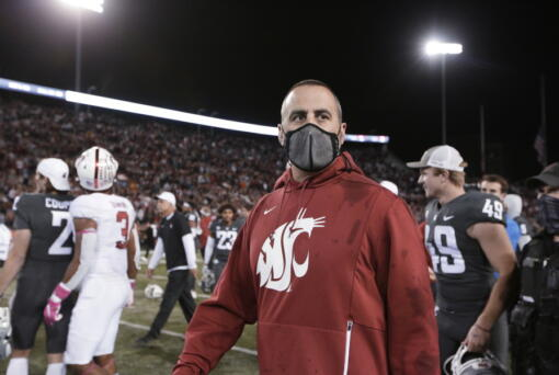 Washington State coach Nick Rolovich walks on the field after the team's NCAA college football game against Stanford, Saturday, Oct. 16, 2021, in Pullman, Wash. Washington State won 34-31.