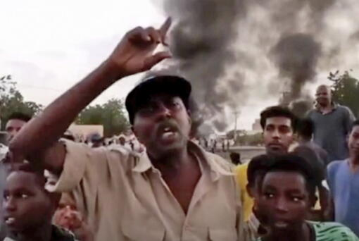 In this frame taken from video people gather during a protest in Khartoum, Sudan, Monday, Oct. 25, 2021. Military forces arrested Sudan's acting prime minister and senior government officials Monday, disrupted internet access and blocked bridges in the capital Khartoum, the country's information ministry said, describing the actions as a coup. In response, thousands flooded the streets of Khartoum and its twin city of Omdurman to protest the apparent military takeover. Footage shared online appeared to show protesters blocking streets and setting fire to tires as security forces used tear gas to disperse them.