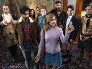 """This image released by CBS shows Utkarsh Ambudkar, foreground left, and Rose McIver in a scene from the comedy series """"Ghosts.""""  (Cliff Lipson/CBS via AP) (Bertrand Calmeau/CBS)"""