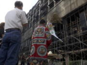A Taoist priest performs rites outside the burnt building in Kaohsiung in southern Taiwan on Friday, Oct. 15, 2021. Taiwanese officials set up an independent commission Friday to investigate the conditions at a run-down building in the port city of Kaohsiung where a fire killed dozens, while authorities scoured the blackened ruins for the cause of the blaze.