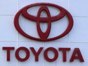 FILE - The Toyota logo is shown on a dealership in Manchester, N.H., in this Thursday, Aug. 15, 2019, file photo. Toyota plans to build a new $1.29 billion factory in the U.S. to manufacture batteries for gas-electric hybrid and fully electric vehicles. The plant location wasn't announced, but the company said it eventually will employ 1,750 people and start making batteries in 2025, gradually expanding through 2031.