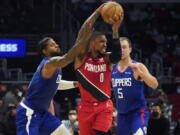 Los Angeles Clippers guard Paul George, left, and guard Luke Kennard (5) defend against Portland Trail Blazers guard Damian Lillard (0) during the first half of an NBA basketball game Monday, Oct. 25, 2021, in Los Angeles.