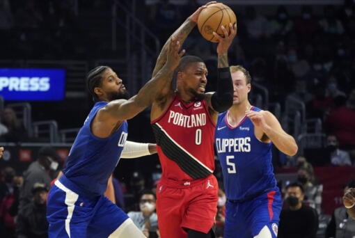 Los Angeles Clippers guard Paul George, left, and guard Luke Kennard (5) defend against Portland Trail Blazers guard Damian Lillard (0) during the first half of an NBA basketball game Monday, Oct. 25, 2021, in Los Angeles. (AP Photo/Marcio Jose Sanchez)