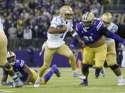UCLA quarterback Dorian Thompson-Robinson (1) keeps the ball as Washington defensive lineman Tuli Letuligasenoa (91) pursues during the first half of an NCAA college football game Saturday, Oct. 16, 2021, in Seattle. (AP Photo/Ted S.